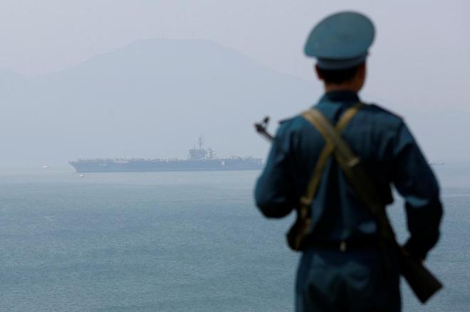 A Vietnamese soldier looks in the direction of the US aircraft carrier Carl Vinson in the city of Danang.