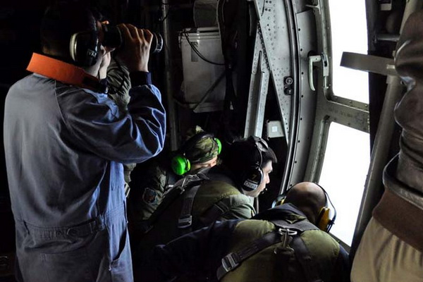 Members of the Argentine Navy look down at the sea from an airplane during a flight to search for the ARA San Juan submarine missing at sea