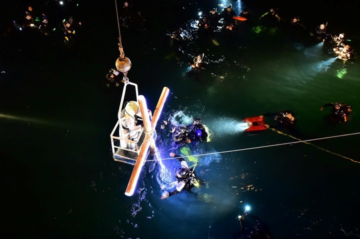 The cross, illuminated from the dock, is lowered on a platform to get lost in the waters of the Golfo Nuevo.
