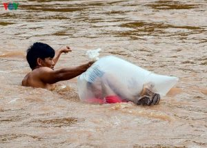 Vietnamese Children Have To Cross A River In Plastic Bags To Get To School